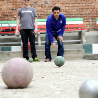 man plays bocce ball on official bocce ball courts in little italy.