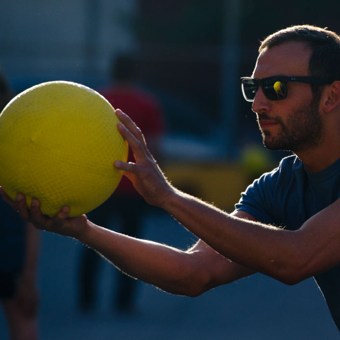 Cool guy in sunglasses about to pitch at SF Kickball